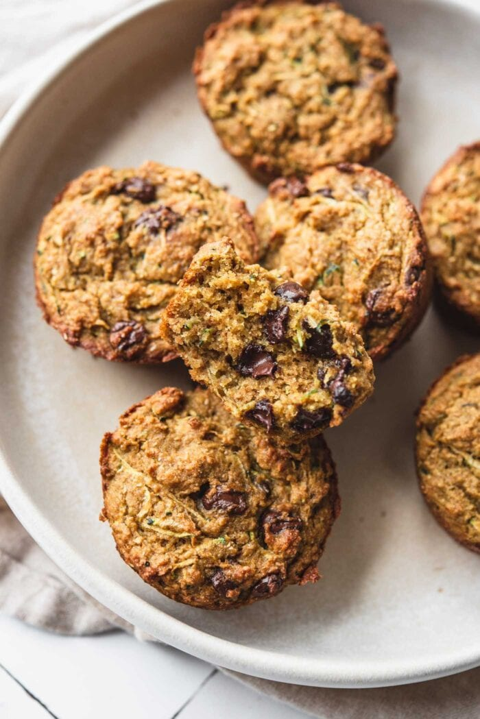 Chocolate chip zucchini muffins on a plate with one cut open to show the inside texture.