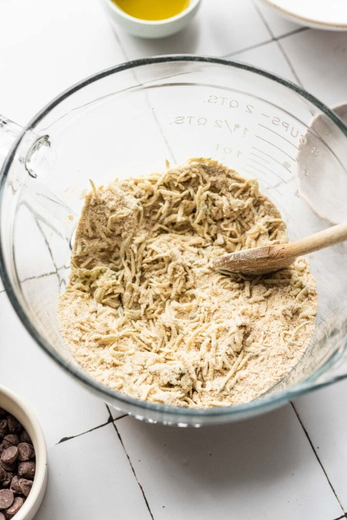 Grated zucchini mixed into flour in a glass mixing bowl.