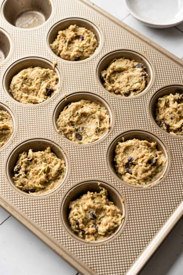 Raw muffing batter scooped into a muffin pan.