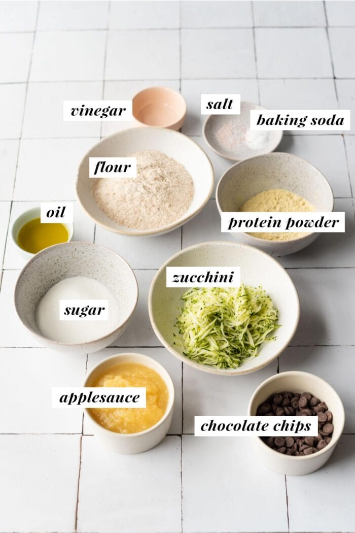 Visual ingredient list for making chocolate chip zucchini protein muffins.