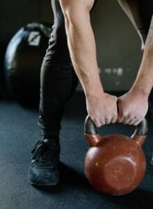 Hands holding the handle of a kettlebell in a deadlift position.
