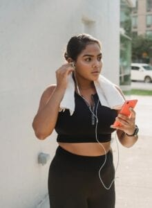 Woman in workout gear with headphones in plugged into an iPhone.