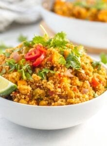 Large bowl of curried quinoa with chickpeas and sweet potato topped with sliced chilis and cilantro.