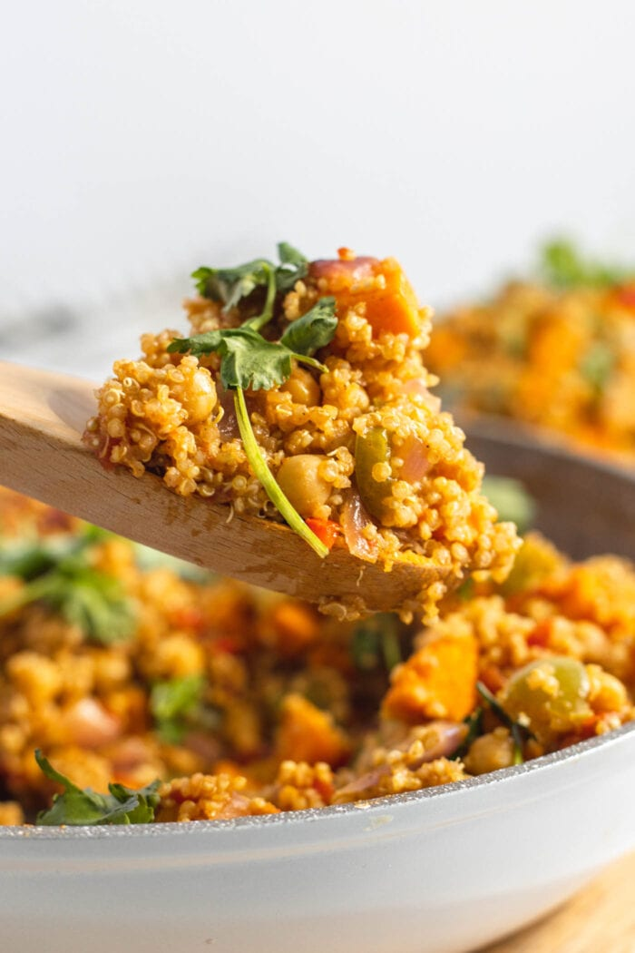 Wooden spoon with a spoonful of curried quinoa on it.