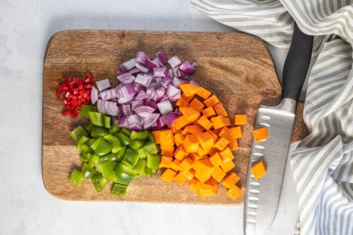 Chopped chili, sweet potato, bell pepper and red onion on a cutting board with a knife.