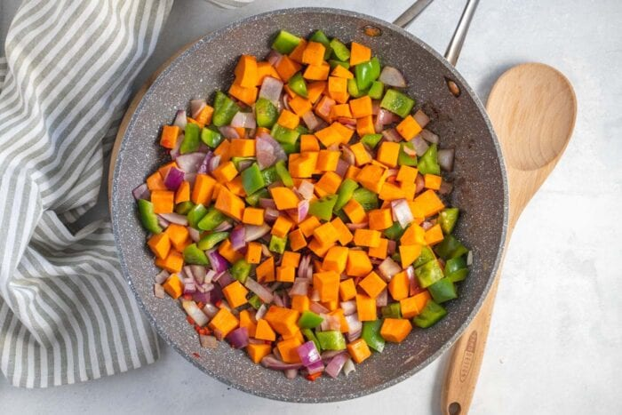 Diced sweet potato, bell pepper and onion cooking in a skillet.