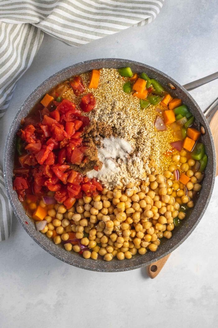Diced tomatoes, quinoa and spices cooking in a large skillet.