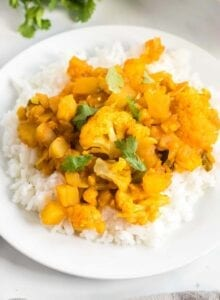 Plate of aloo gobi or curried potato and cauliflower served over a bed of jasmine rice.