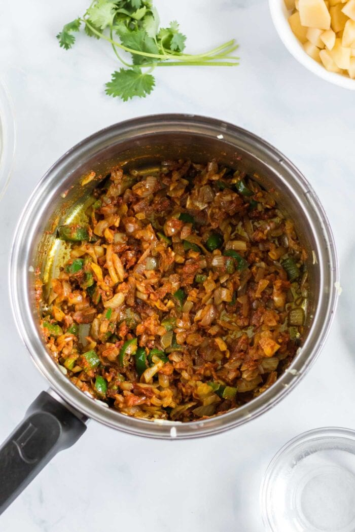 Diced onion, garlic and ginger coated in spices in a pot.