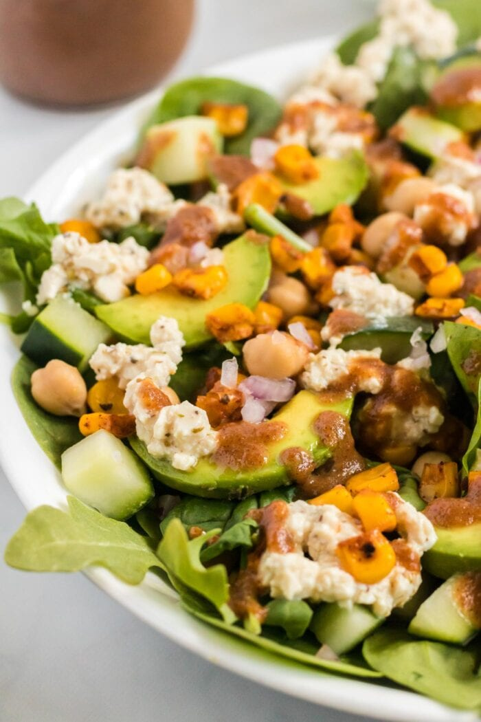Close up of avocado slices in a salad with corn and chickpeas.