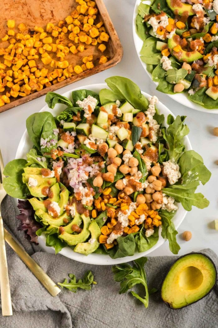 Overhead view of a salad with avocado, corn, chickpeas and feta.