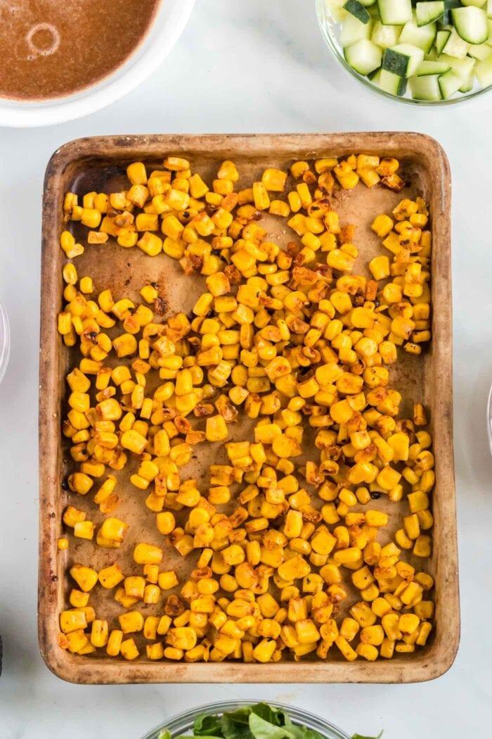 Roasted corn on a baking sheet.