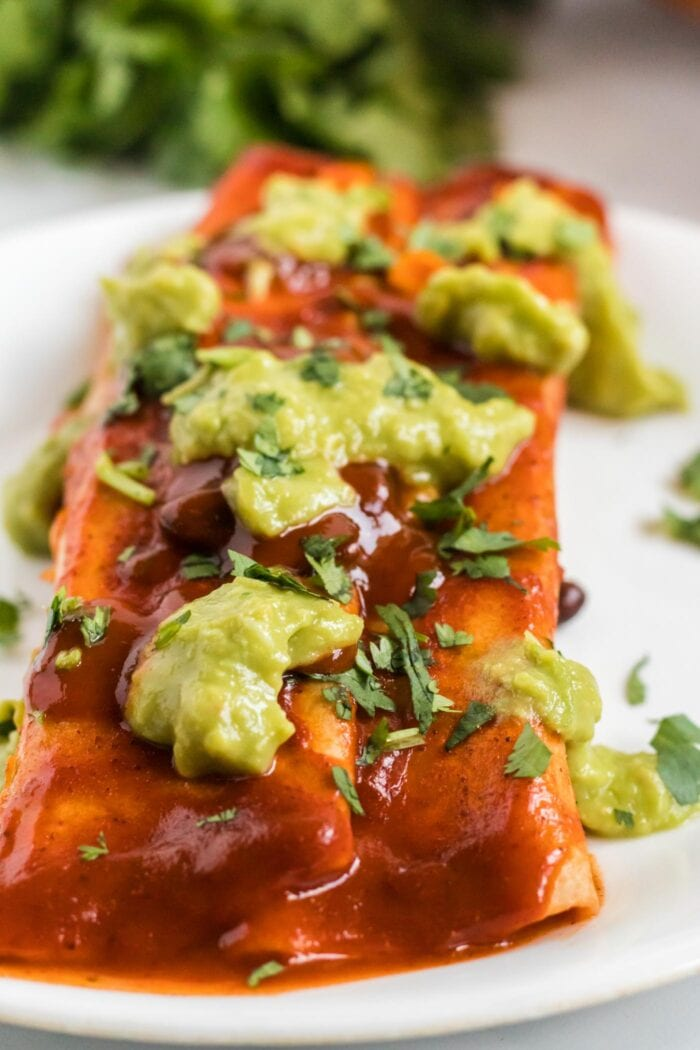 Close up of an enchilada topped with guacamole on a plate.