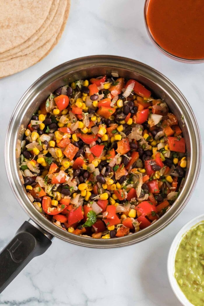 Corn, bell peppers and black beans cooking in a large skillet.