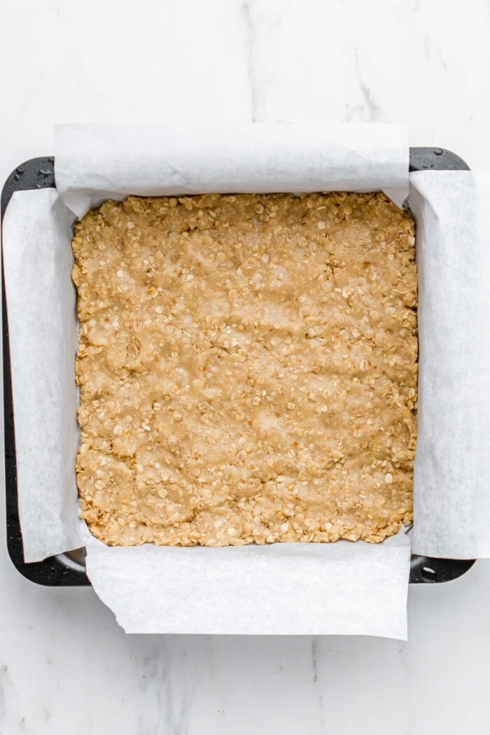 Raw oatmeal bar batter pressed into a baking pan.