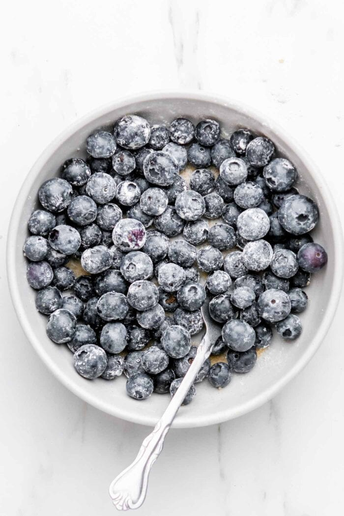 Blueberries coated in cornstarch in a bowl.