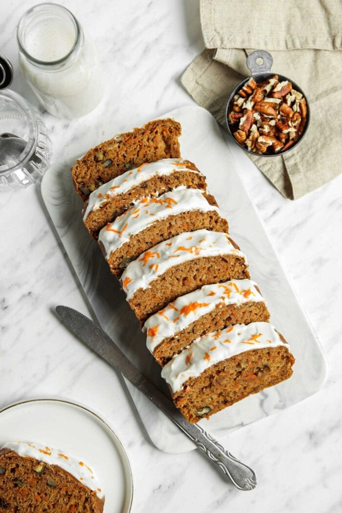 Overhead view of a sliced carrot banana bread topped with frosting on a marble cutting board.