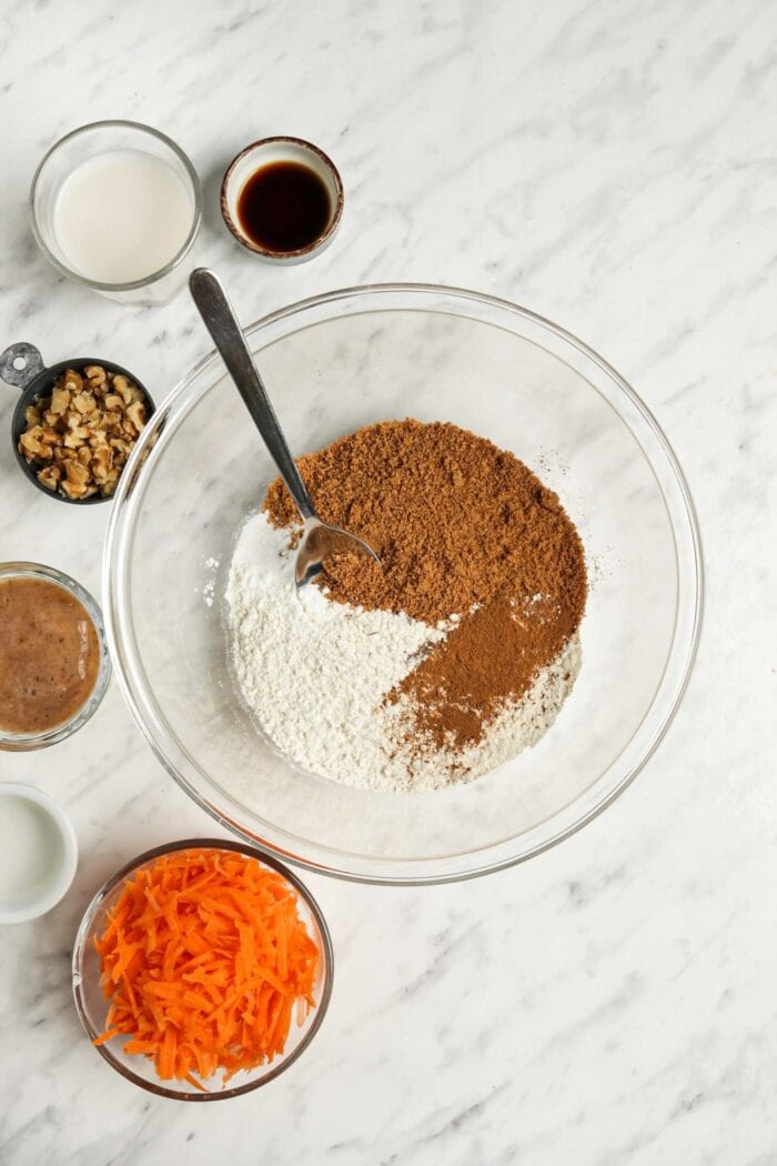 Dry baking ingredients like flour and sugar in a glass mixing bowl with a spoon.