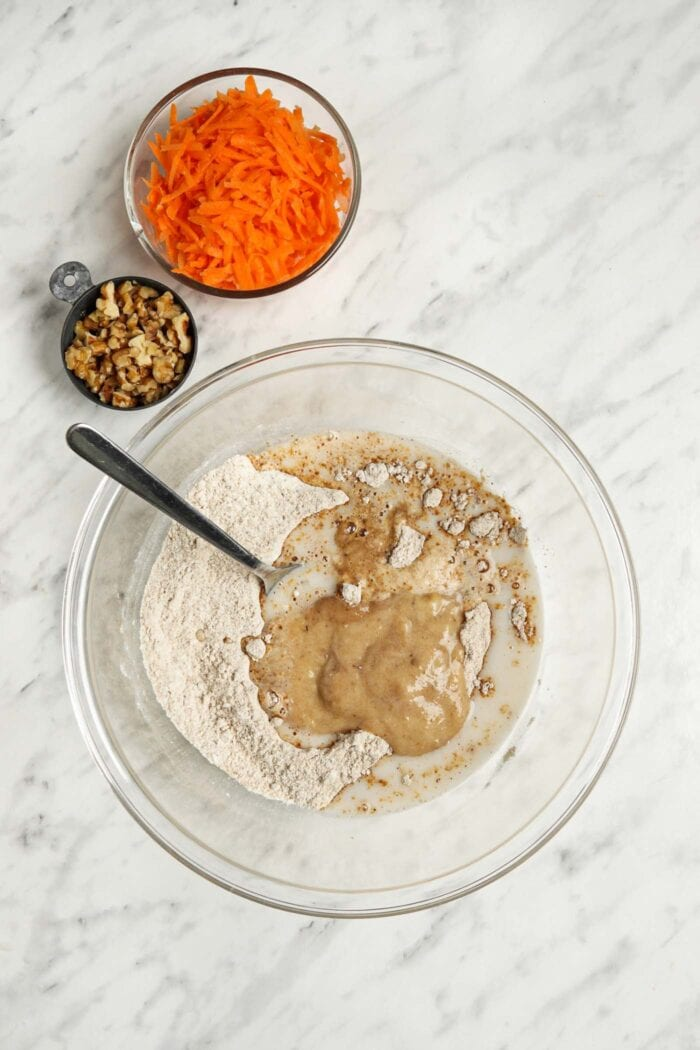 Wet ingredients like milk and mashed banana added to flour in a glass mixing bowl.