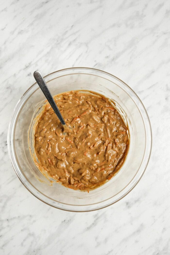 Raw carrot cake banana bread batter in a glass mixing bowl.