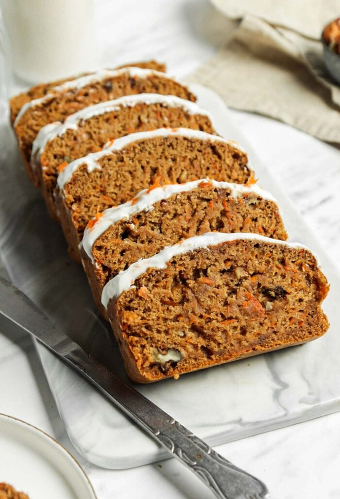 Sliced vegan carrot cake banana bread topped with cream cheese frosting on a marble cutting board.