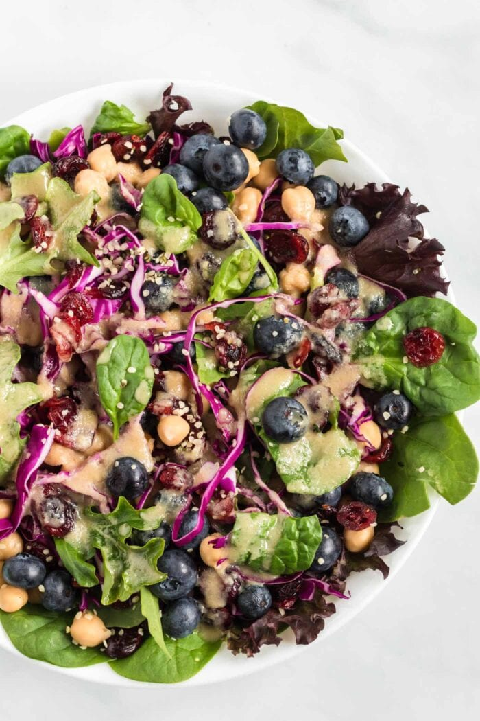 Close up overhead view of a colourful salad with greens, cabbage and blueberries.