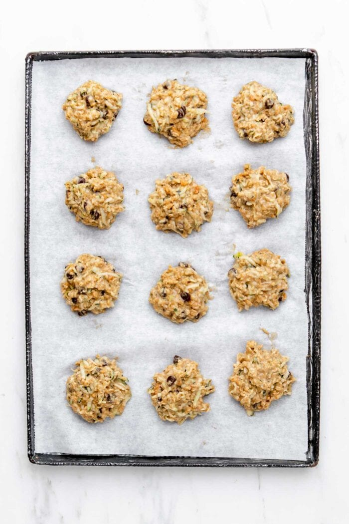 Raw chocolate chip zucchini cookies on a baking tray.
