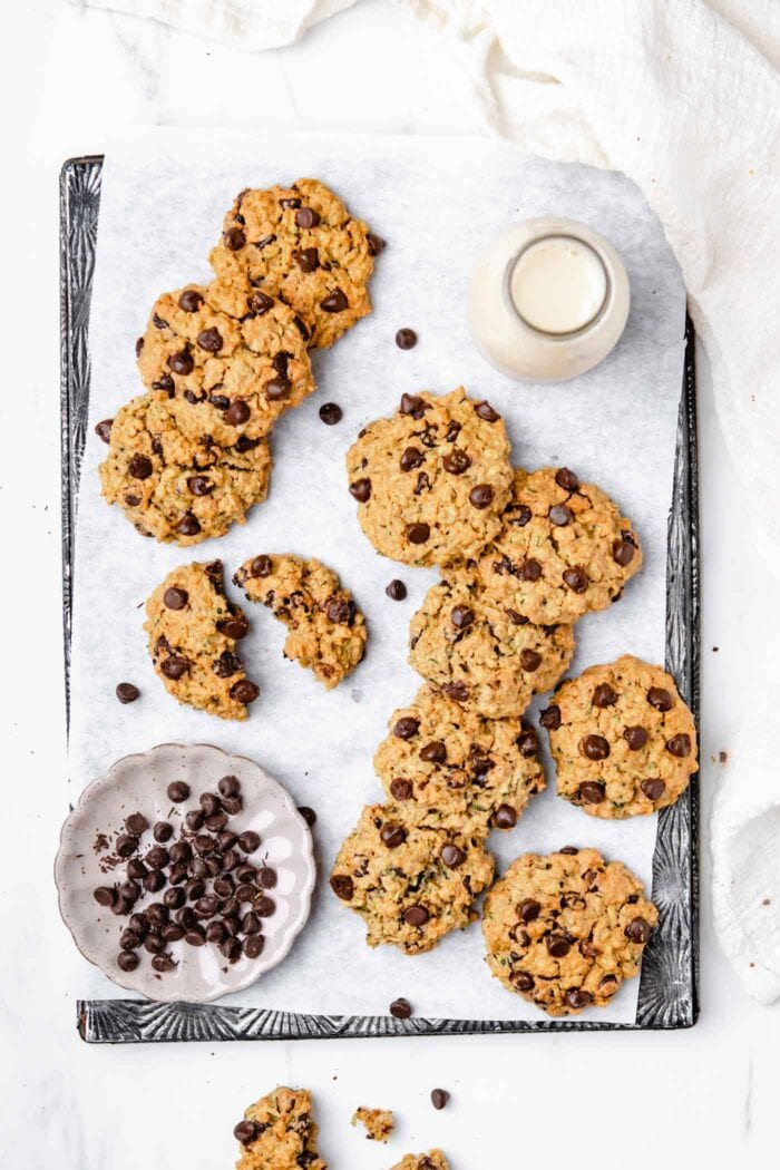 Chocolate chip zucchini cookies scattered around a baking tray.