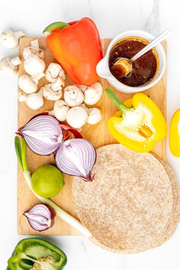 Overhead view of various vegetables on a cutting board with some marinade in a bowl and a wheat tortilla.