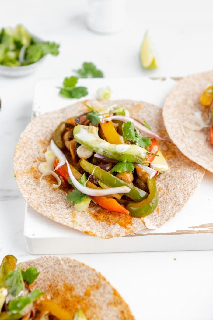 Tortilla filled with bell peppers, onion and avocado on a cutting board.