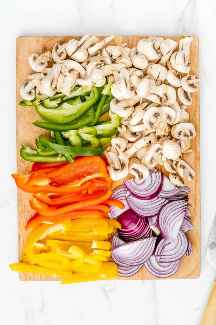 Sliced mushooms, onion and bell pepper on a cutting board.