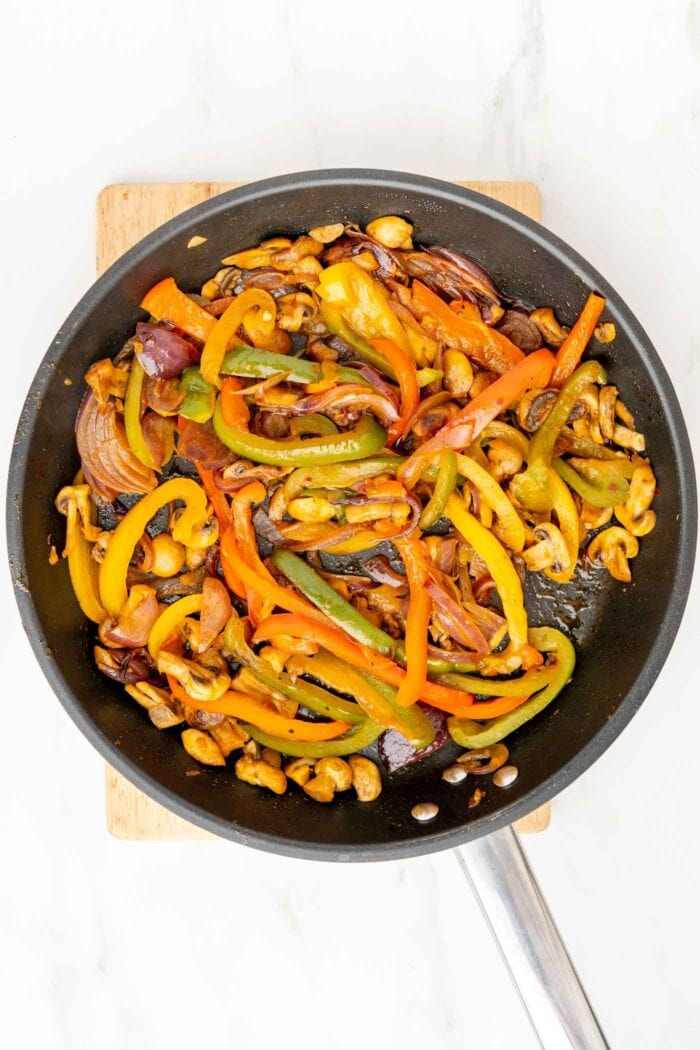 Cooked fajita vegetables in a large skillet.