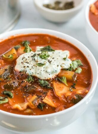 Bowl of lasagna soup topped with tofu ricotta and fresh basil.