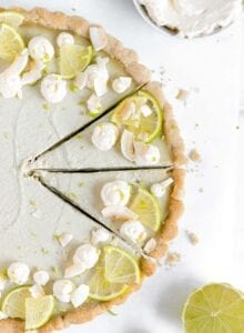 Overhead view of a vegan key lime pie topped with lime wedges and coconut whipped cream.