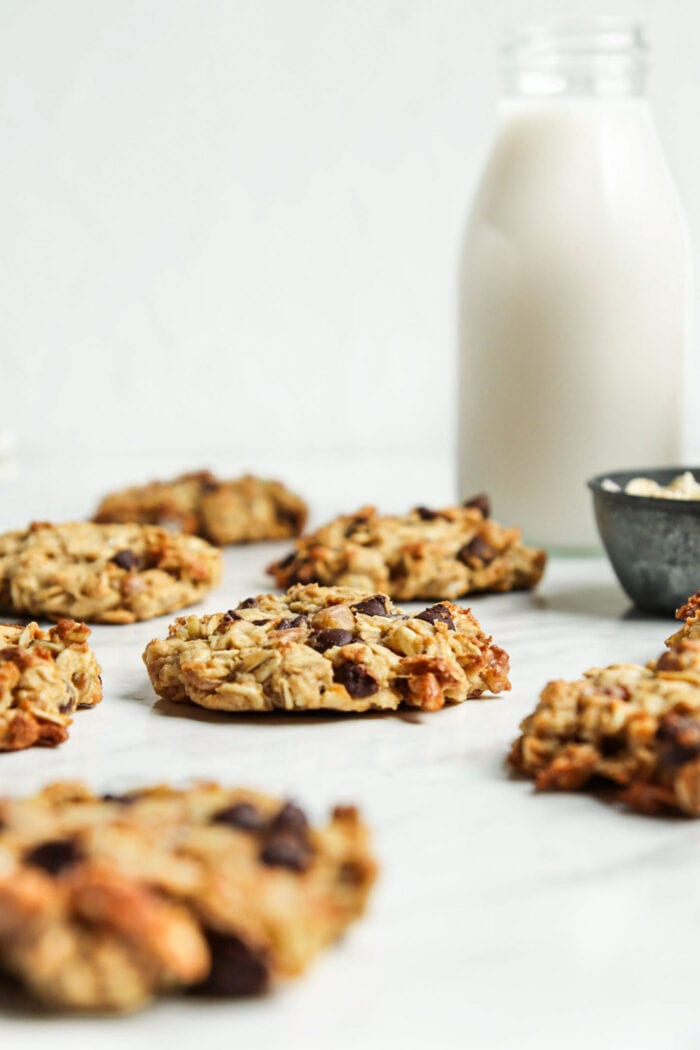 Chocolate chip oatmeal cookies scattered around on a marble surface with a glass of milk in the background.