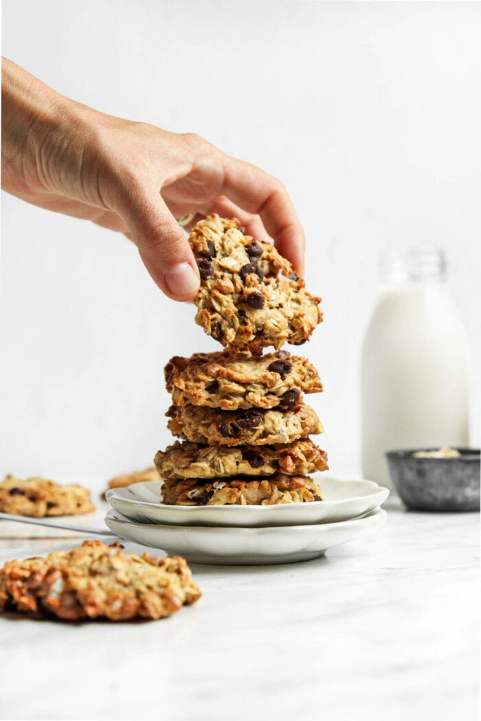 Hand picking a chocolate chip cookie from a stack of cookies on a plate.