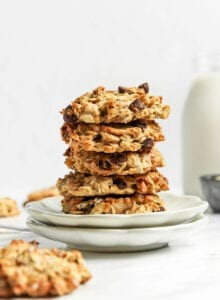 Stack of 3 oatmeal chocolate chip cookies on a small white plate.