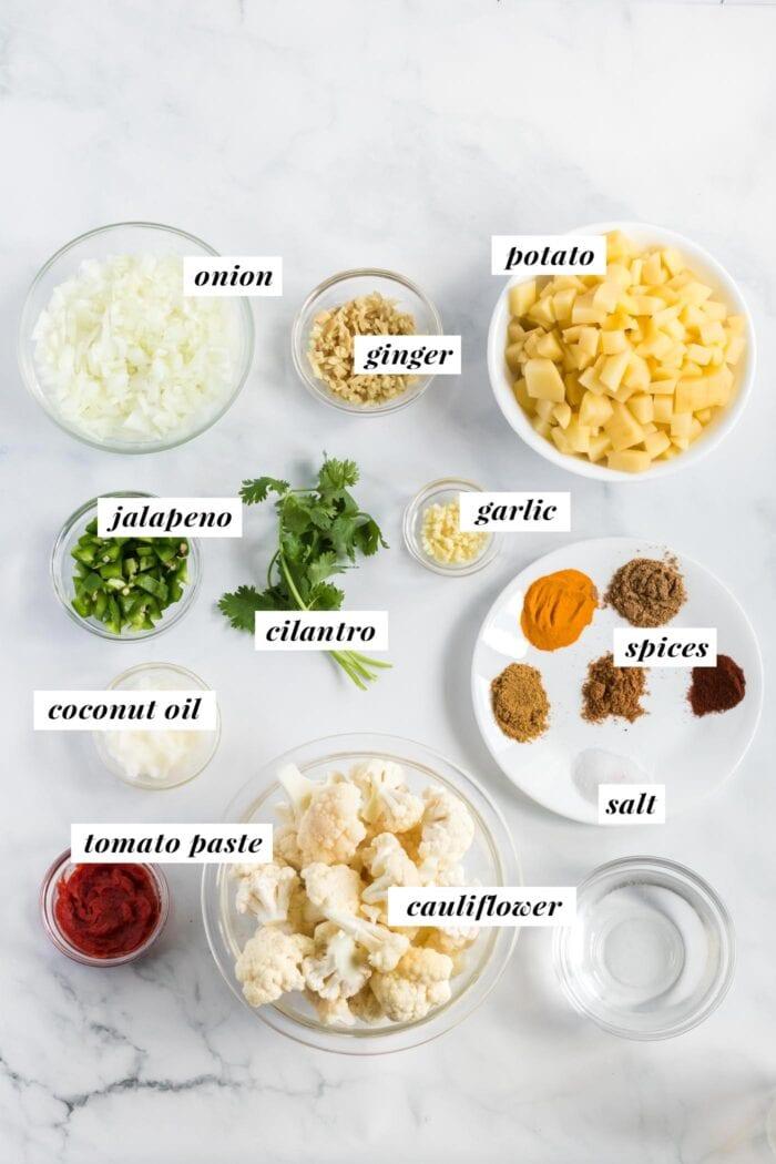 Visual list of ingredients for an aloo gobi curried cauliflower potato recipe.