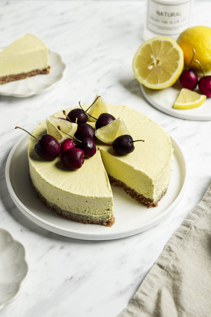 Lemon cheesecake topped with cherries with a slice cut out of it.