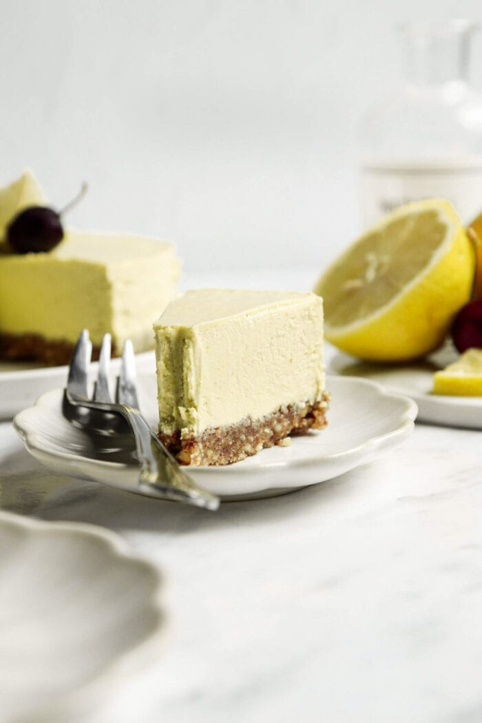 Thick slice of lemon cheesecake on a plate with a fork.