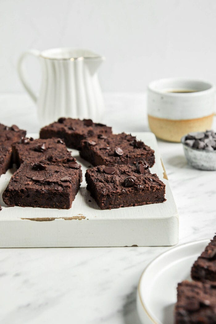 A number of chocolate chip brownies on a cutting board.