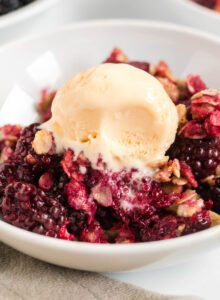 Blackberry crumble topped with a scoop of vanilla ice cream in a bowl.