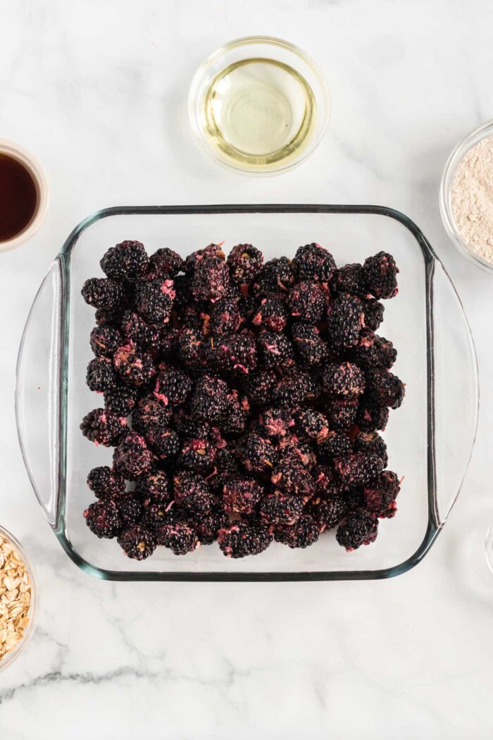 Blackberries layered in a glass baking dish.