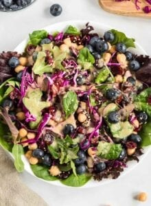 Overhead view of a colourful salad with greens, cabbage and blueberries.