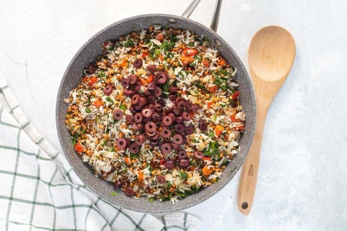 Olives added to a skillet of rice, lentils and vegetables.
