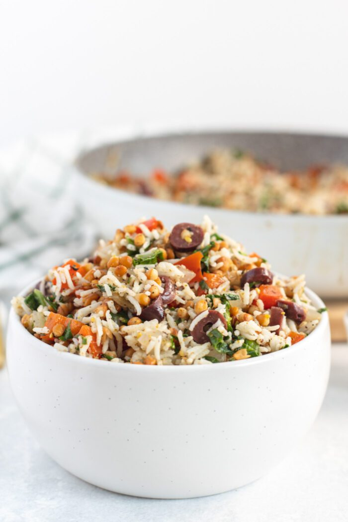 Bowl of rice and lentils with spinach and olives.