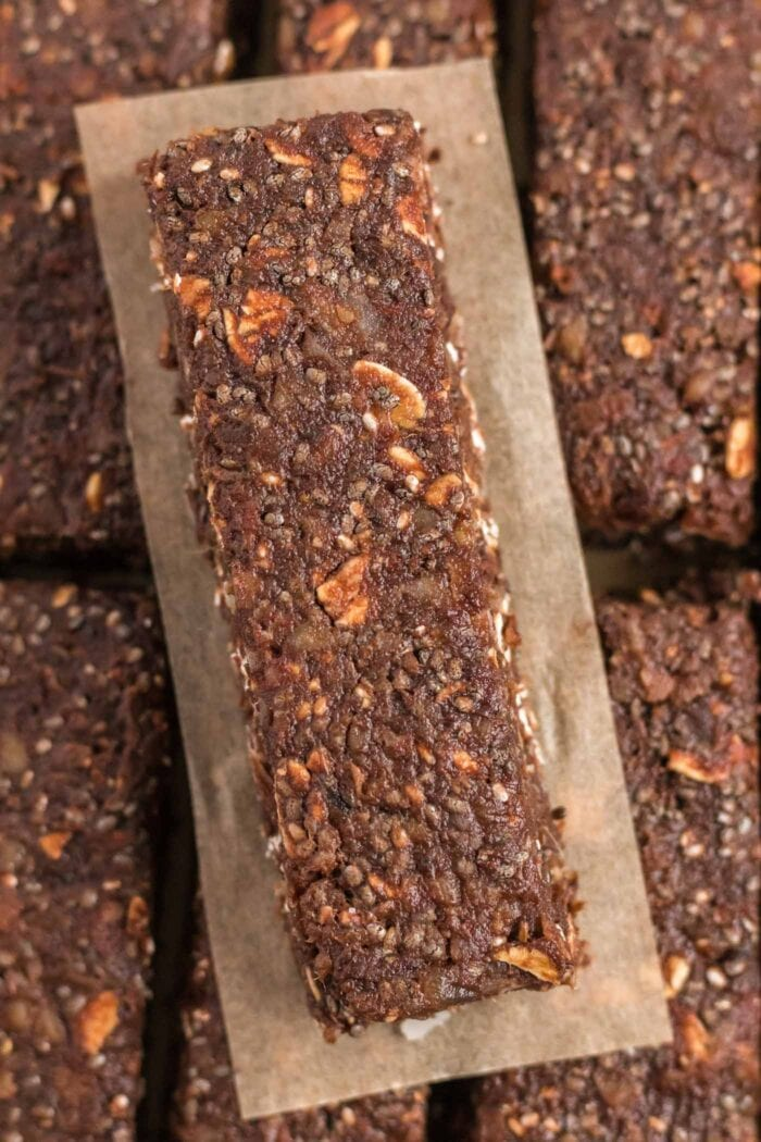 Overhead view of a chocolate chia seed bar on a piece of parchment paper.