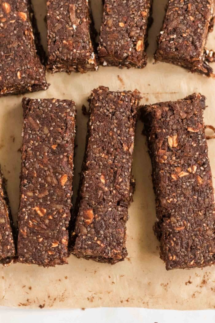 Close up of 3 chocolate energy bars on parchment paper.