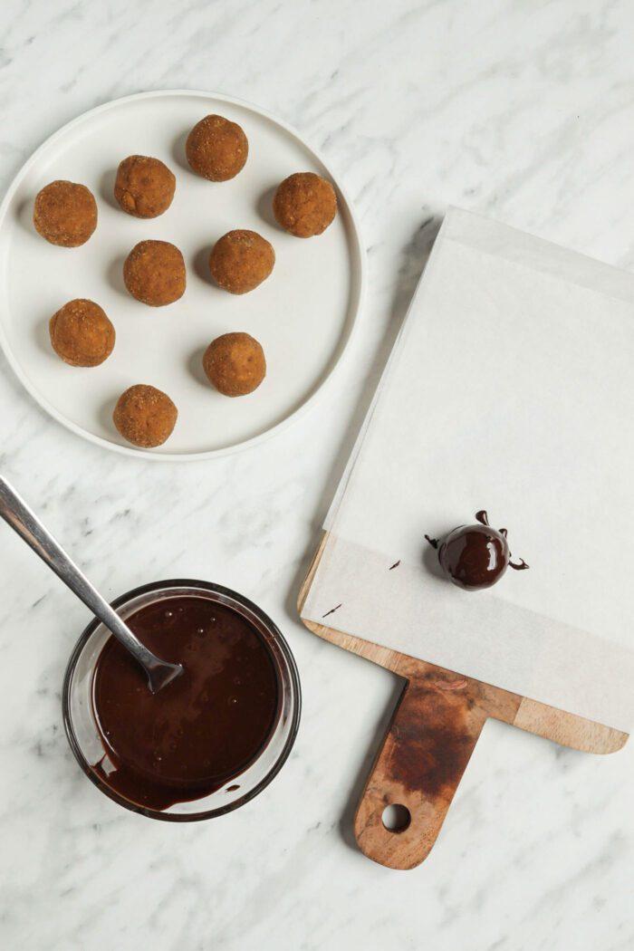 Pumpkin balls being rolled in chocolate.