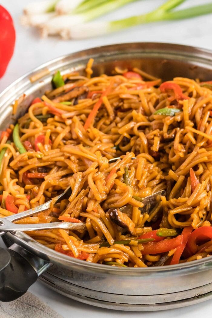 Close up of vegetable lo mein cooking in a large frying pan with a pair of tons in the pan.